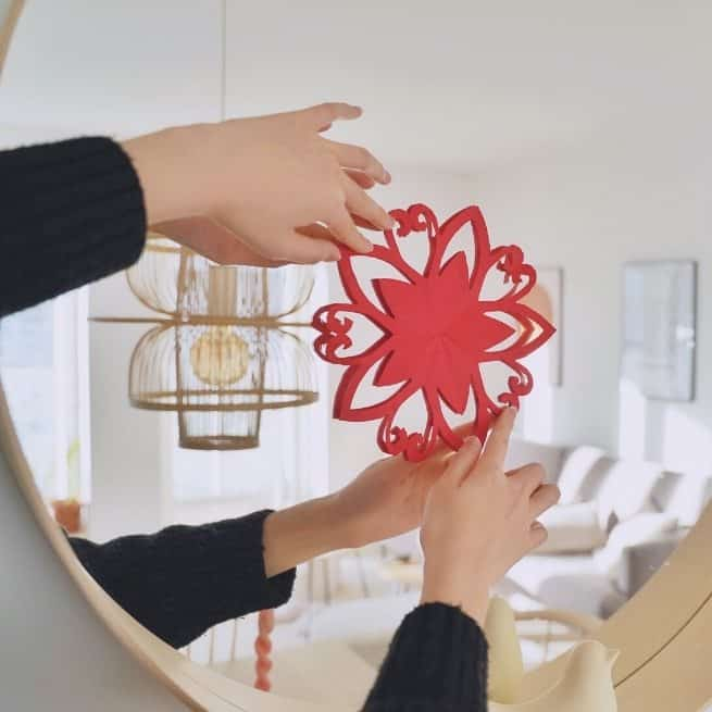 Traditional red Chinese paper cutout held on a mirror
